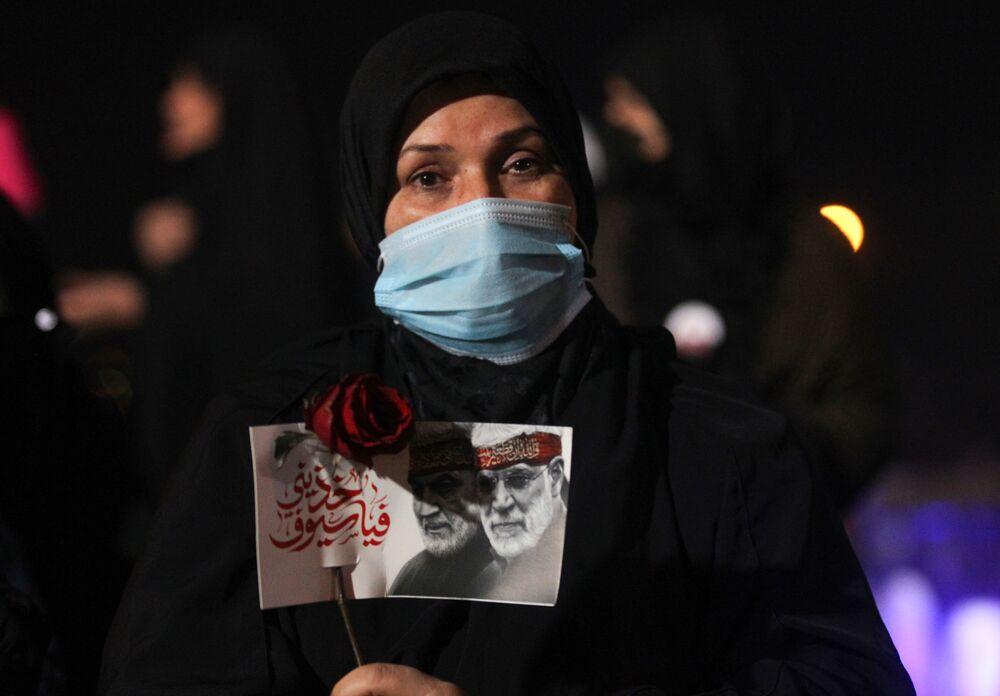 Donna con un ritratto del comandante iraniano Qasem Soleimani e del comandante iracheno Abu Mahdi al-Muhandis a Baghdad