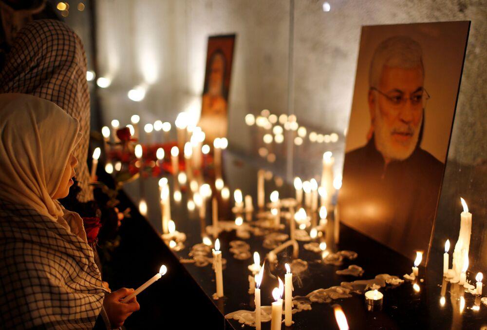 Donna davanti alle candele nel primo anniversario della morte del comandante iraniano Qasem Soleimani e del comandante iracheno Abu Mahdi al-Muhandis a Baghdad