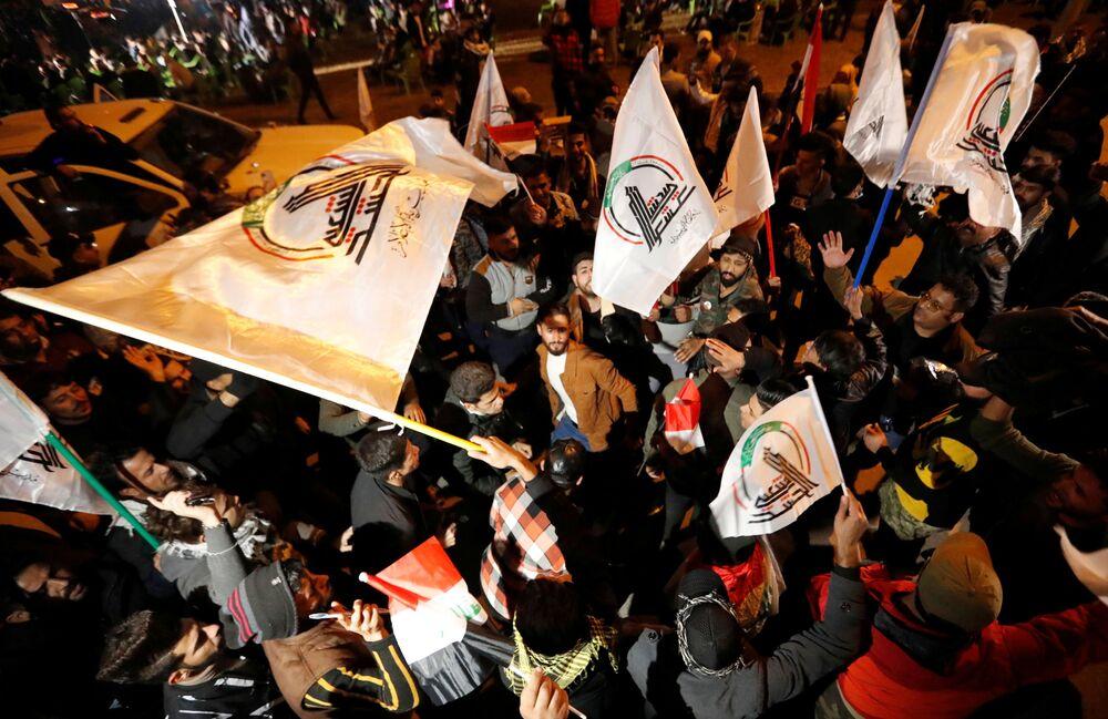 Persone con bandiere durante il primo anniversario della morte del comandante iraniano Qasem Soleimani e del comandante iracheno Abu Mahdi al-Muhandis a Baghdad