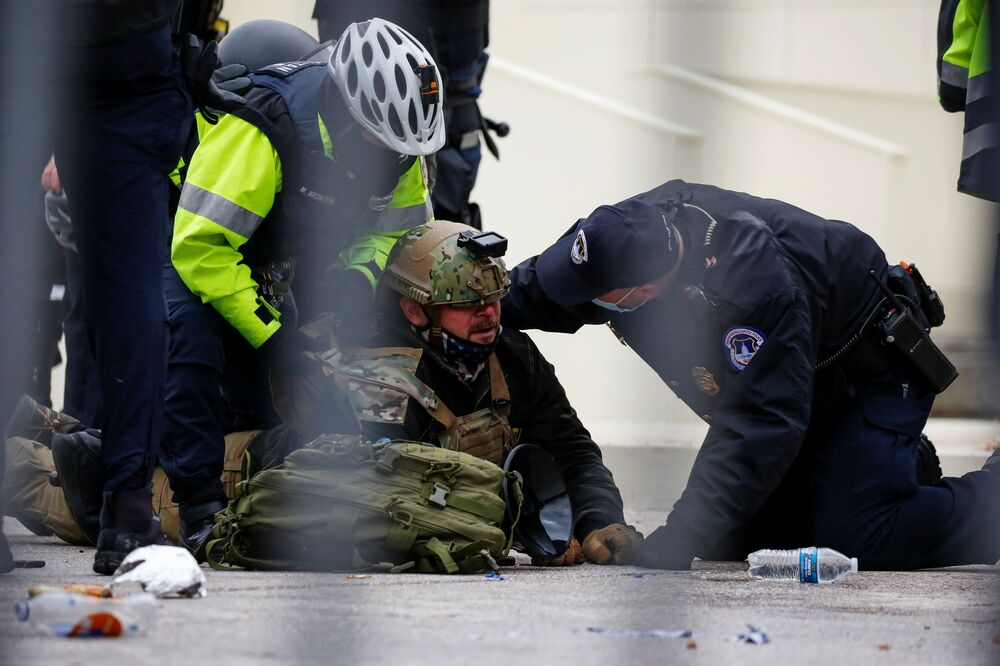 Gli agenti di polizia arrestano un sostenitore del presidente in carica Donald Trump nel corso delle proteste vicino al Campidoglio.