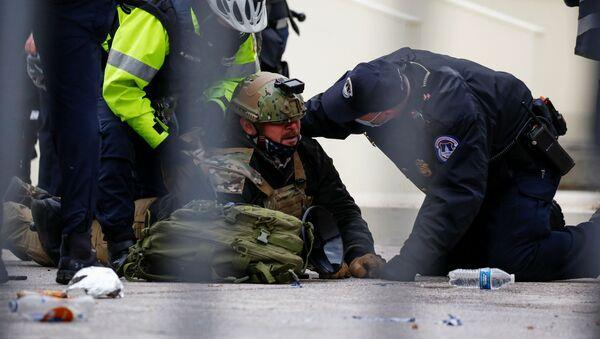Gli agenti di polizia arrestano un sostenitore del presidente in carica Donald Trump nel corso delle proteste vicino al Campidoglio. - Sputnik Italia