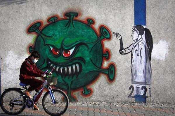 Un murale che raffigura un'operatrice sanitaria che fa iniettt il vaccino anti-Covid,  città di Gaza, 31 dicembre 2020.  - Sputnik Italia