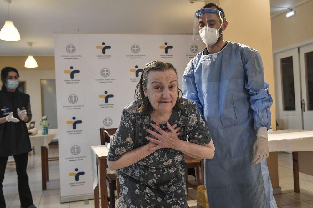 Una donna anziana sta ringraziando il personale dopo essere stata vaccinata in una casa di riposo nei dintorni di Atene, Grecia, 4 gennaio 2021.