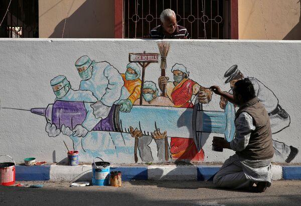 Un uomo sta dipingendo un murale che raffigura il vaccino anti-Covid, Calcutta, India, 2 gennaio 2021.  - Sputnik Italia