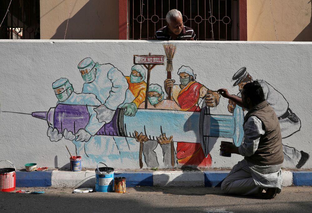 Un uomo sta dipingendo un murale che raffigura il vaccino anti-Covid, Calcutta, India, 2 gennaio 2021.