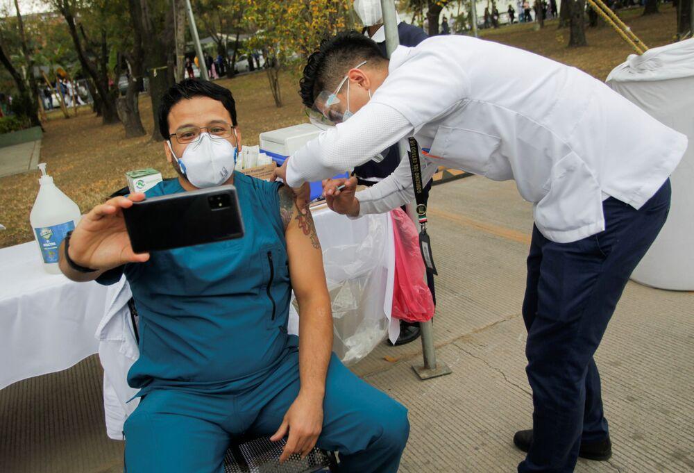 Un operatore sanitario si fa un selfie mentre si sottopone al vaccino anti-Covid in un ospedale militare a San Nicolas de los Garza, Messico, 29 dicembre 2020.