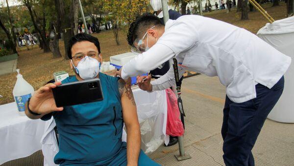 Медицинский работник делает селфи во время инъекции вакцины от COVID-19 в военном госпитале в Сан-Николас-де-лос-Гарса, Мексика - Sputnik Italia