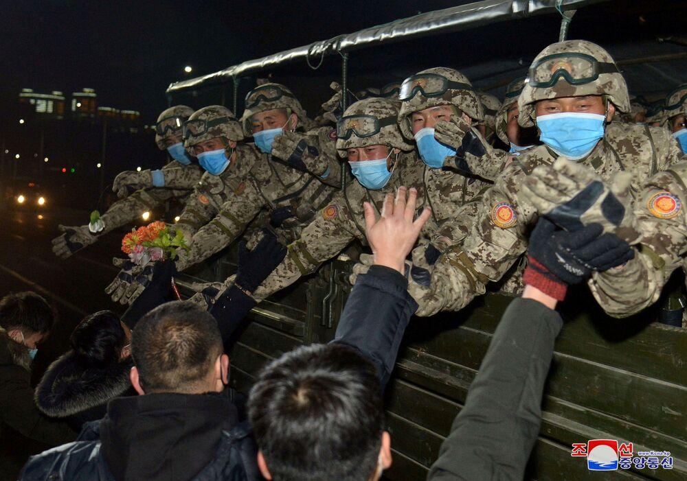 La gente saluta i partecipanti alla parata militare a Pyongyang, Corea del Nord.