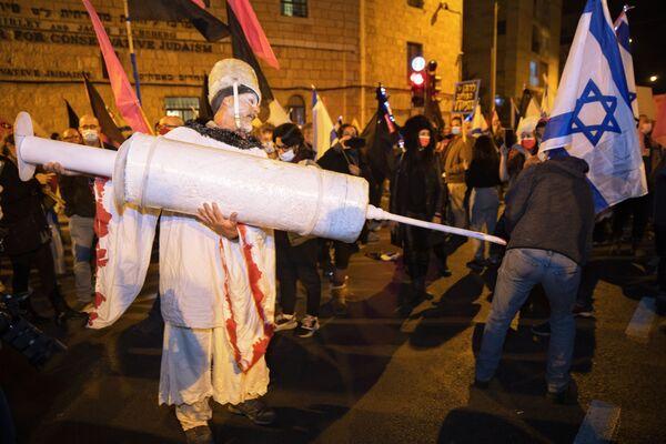 Un residente di Israele tiene un'enorme siringa nel corso delle proteste contro il lockdown, Gerusalemme.  - Sputnik Italia