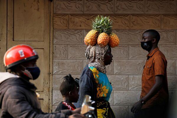 Una donna porta gli ananas sulla sua testa, Kampala, Uganda.  - Sputnik Italia