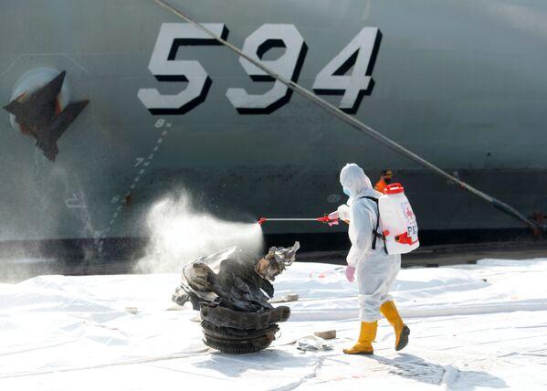 Un dipendente della Croce Rossa spruzza una sostanza disinfettante su un frammento dell'aereo Sriwijaya Air.  - Sputnik Italia