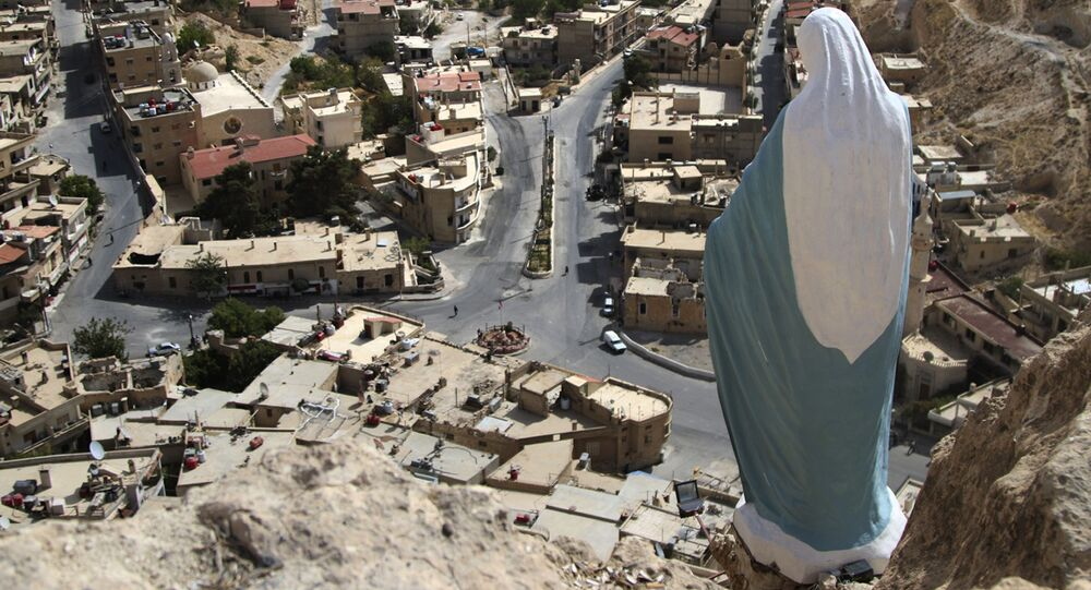 In this photo taken on Sunday, Oct. 18, 2015, a statue of the Virgin Mary overlooks the village of Maaloula, north of Damascus, Syria