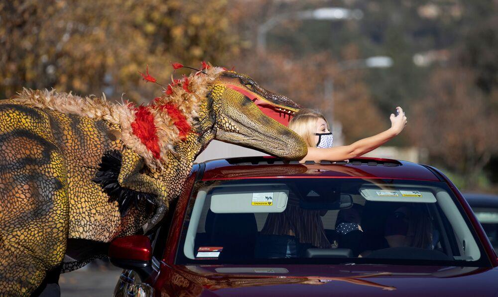 La ragazza fa un selfie con un uomo in costume da dinosauro