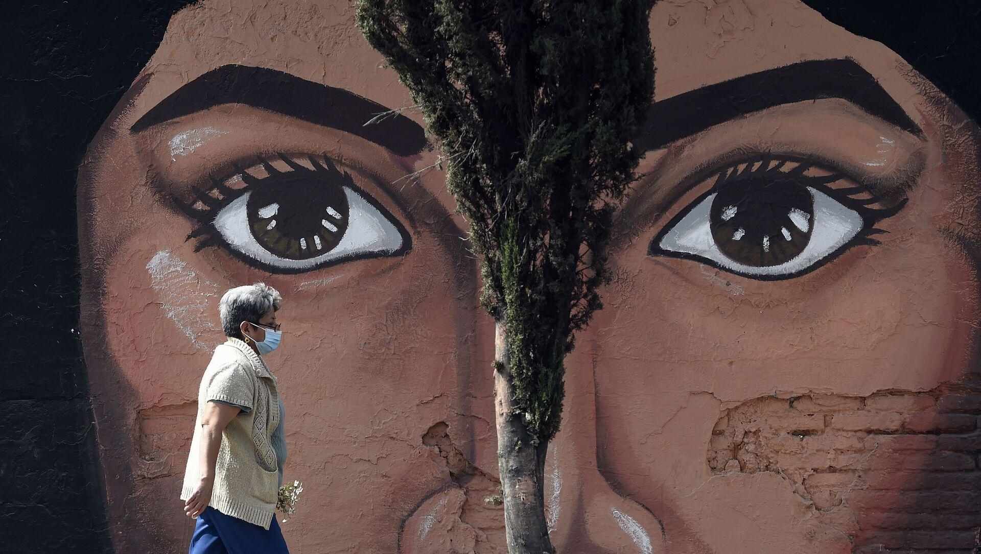 Женщина  проходит мимо граффити на одной из стен кладбища San Nicolas Tolentino в муниципалитете Истапалапа в Мехико - Sputnik Italia, 1920, 19.02.2021