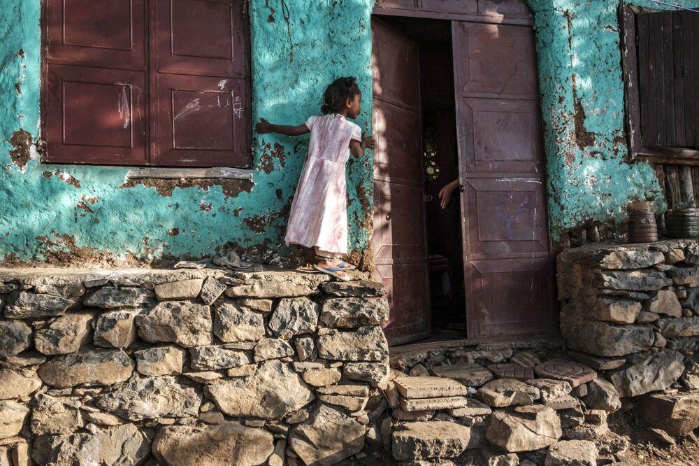 Una ragazza guarda attraverso una porta aperta nella città di Gondar, in Etiopia