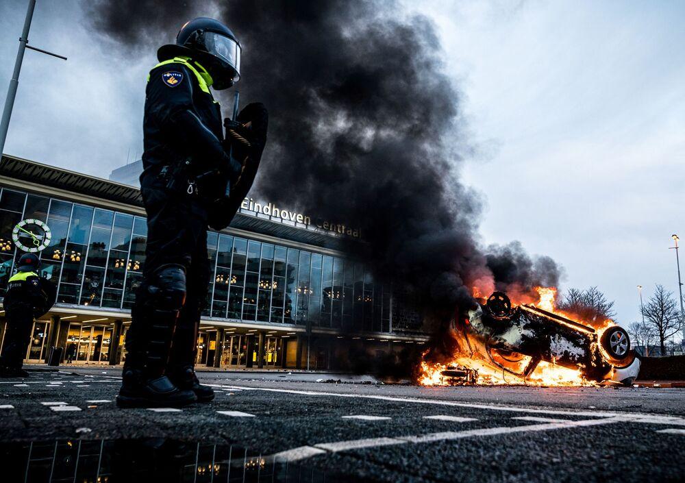 Un'auto in fiamme davanti alla stazione ferroviaria di Eindhoven, incendiata durante le proteste nei Paesi Bassi