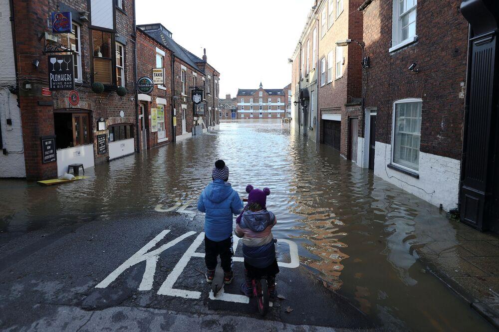 Due bambini in una strada allagata a York, Regno Unito
