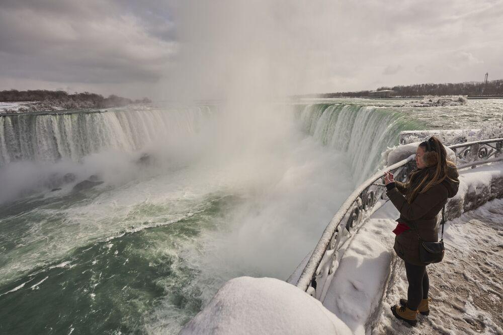 Una donna sta fotografando Horseshoe Fall, la più grande delle tre cascate che compongono il complesso del Niagara, Ontario, Canada. Si vede il vapore che sale dalle cascate.