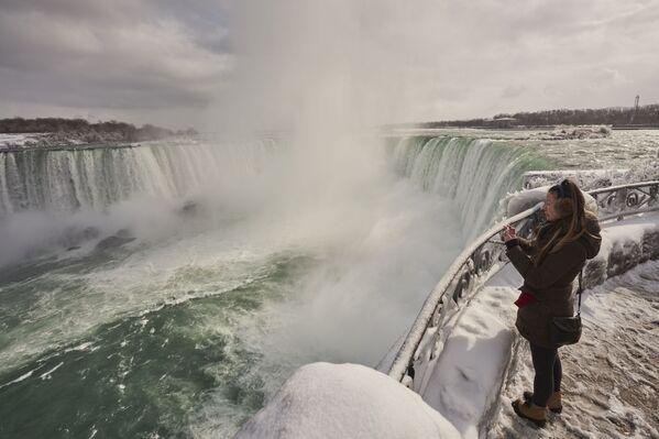 Una donna sta fotografando Horseshoe Fall, la più grande delle tre cascate che compongono il complesso del Niagara, Ontario, Canada. Si vede il vapore che sale dalle cascate. - Sputnik Italia