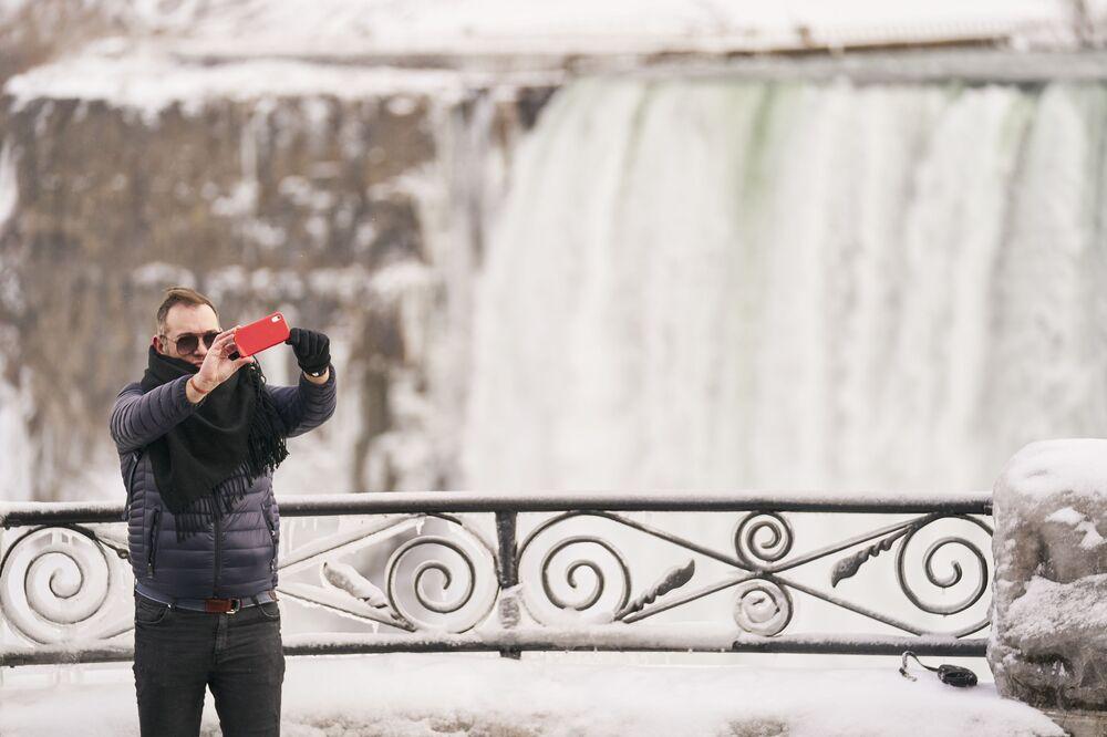 Un uomo sta facendo una foto selfie sullo sfondo di Horseshoe Fall, la più grande delle tre cascate che compongono il complesso del Niagara, Ontario, Canada.