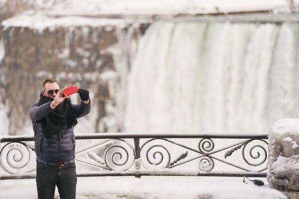 Un uomo sta facendo una foto selfie sullo sfondo di Horseshoe Fall, la più grande delle tre cascate che compongono il complesso del Niagara, Ontario, Canada. - Sputnik Italia