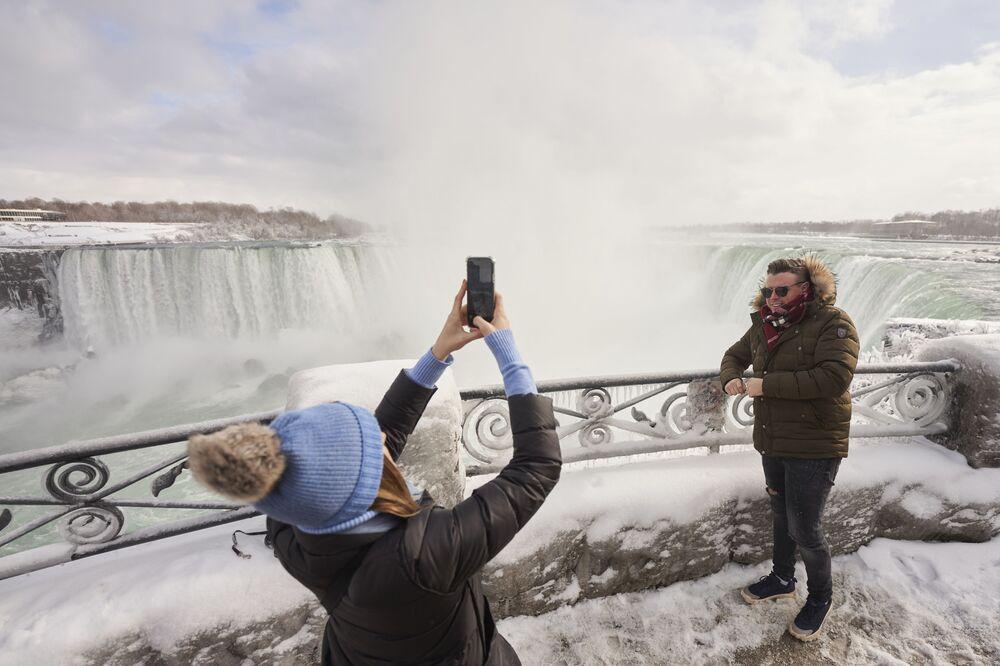 Una donna sta facendo una foto di un uomo sullo sfondo di Horseshoe Fall, la più grande delle tre cascate che compongono il complesso del Niagara, Ontario, Canada.