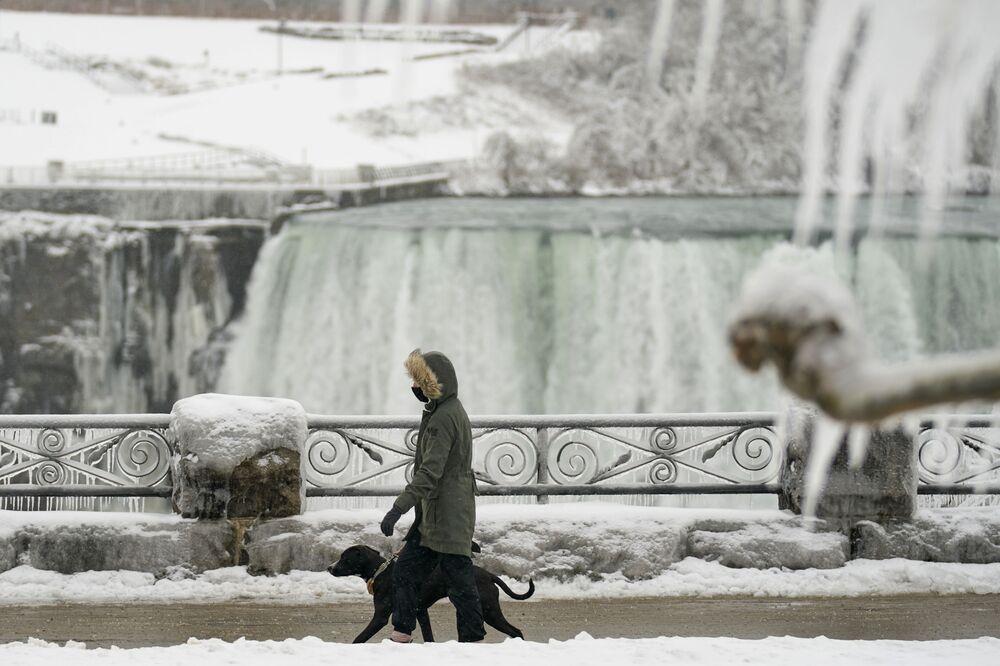 Una donna fa una passeggiata con il suo cane lungo le cascate del Niagara, Ontario, Canada.