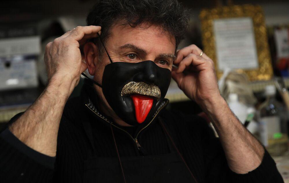 Gualtiero Dall'Osto, artigiano veneziano di maschere di carnevale, indossa una delle sue creazioni nella sua bottega a Venezia, Italia, sabato 30 gennaio 2021