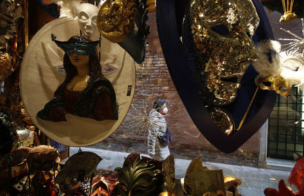 Una donna che indossa una mascherina cammina accanto a un negozio di maschere di carnevale a Venezia, Italia, sabato 30 gennaio 2021. Il carnevale avrebbe dovuto iniziare sabato, ma la pandemia COVID-19 ha reso quella festa annuale impossibile.