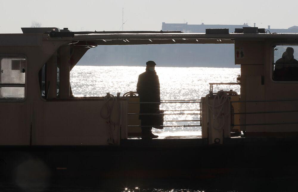 Un uomo in una mascherina protettiva in attesa di un vaporetto a Venezia