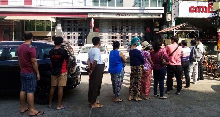 Persone in fila davanti ad una banca a Yangon in Myanmar