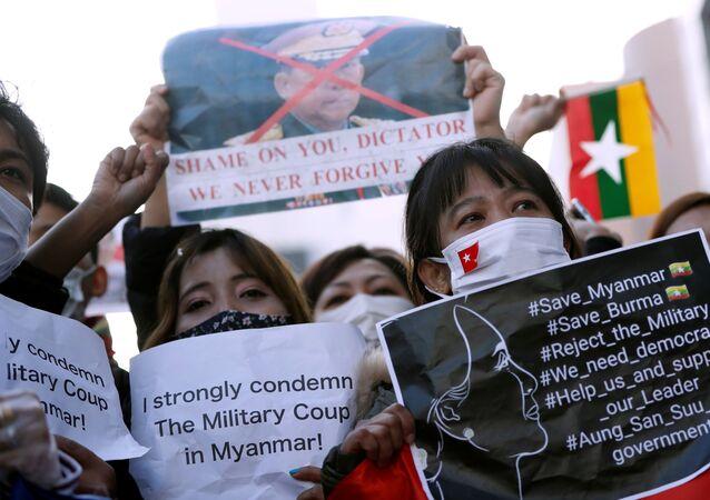 I manifestanti del Myanmar residenti in Giappone tengono cartelli in una manifestazione contro i militari del Myanmar presso L'Università delle Nazioni Unite a Tokyo