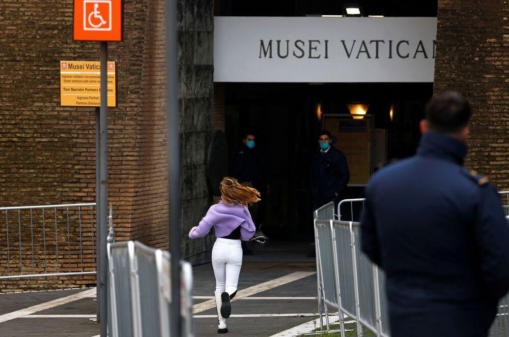 La ragazza corre all'ingresso dei Musei Vaticani