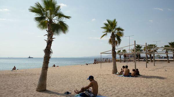 Bagnanti a distanza in una spiaggia vicino ad Atene la scorsa estate - Sputnik Italia