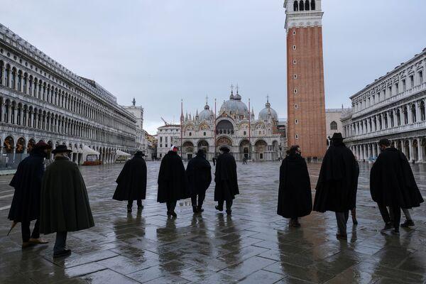 Le persone che indossano il tradizionale tabarro, un lungo mantello nero, si riuniscono in piazza San Marco il giorno in cui doveva iniziare il Carnevale di Venezia, con l'evento annuale annullato a causa della pandemia del coronavirus (COVID-19), a Venezia, Italia, il 31 gennaio 2021 - Sputnik Italia
