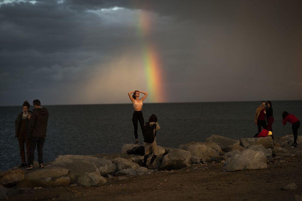 Le persone posano per le foto dopo una tempesta a Barcellona, Spagna