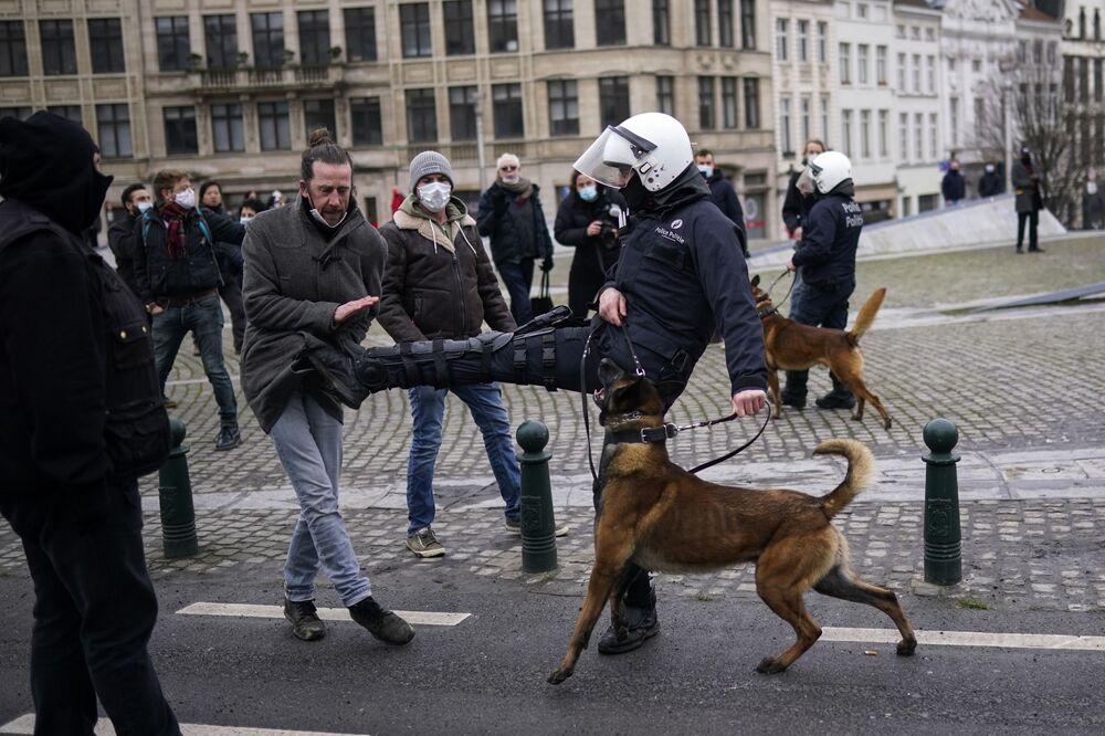 Un agente di polizia prende a calci un manifestante durante una manifestazione non autorizzata contro le misure restrittive COVID-19 a Bruxelles, domenica 31 gennaio 2021
