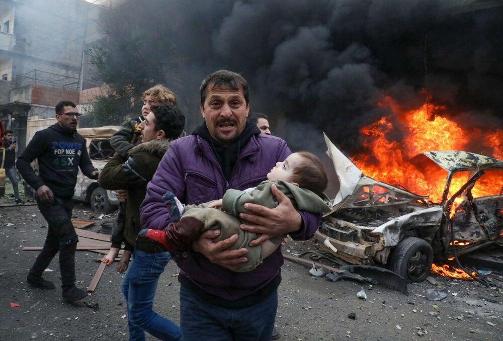 I civili trasportano una giovane vittima dopo un'esplosione nella città di Azaz, nella provincia di Aleppo, in Siria, il 31 gennaio 2021. Un'autobomba ha ucciso almeno quattro persone, tra cui tre civili.