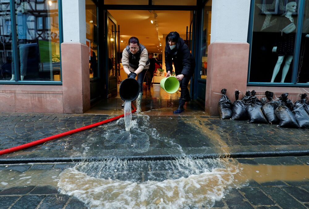I dipendenti di un negozio di abbigliamento puliscono il loro negozio allagato dopo che le inondazioni a causa delle forti piogge e dello scioglimento della neve hanno colpito la città di Buedingen vicino a Francoforte, in Germania, il 30 gennaio 2021