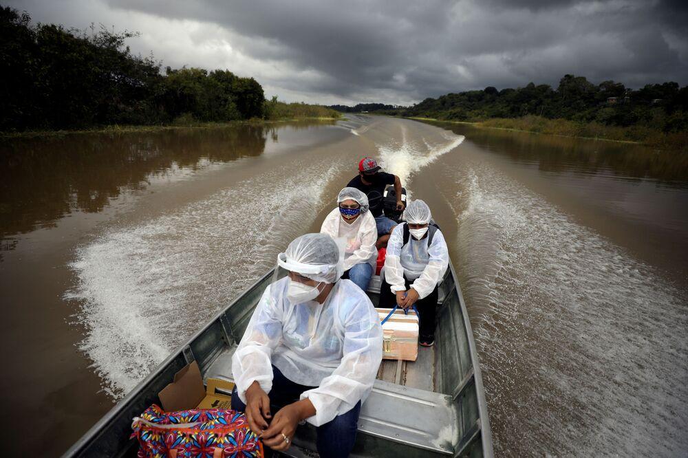 Gli operatori sanitari municipali viaggiano su una barca lungo le rive del fiume Solimoes, dove vivono Ribeirinhos (abitanti del fiume), per somministrare il vaccino AstraZeneca/Oxford contro la malattia da coronavirus (COVID-19) ai residenti, a Manacapuru, Brasile