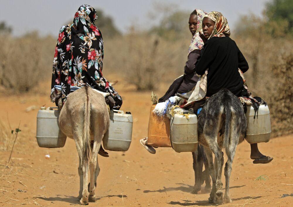 Le donne sudanesi trasportano l'acqua sugli asini in un villaggio