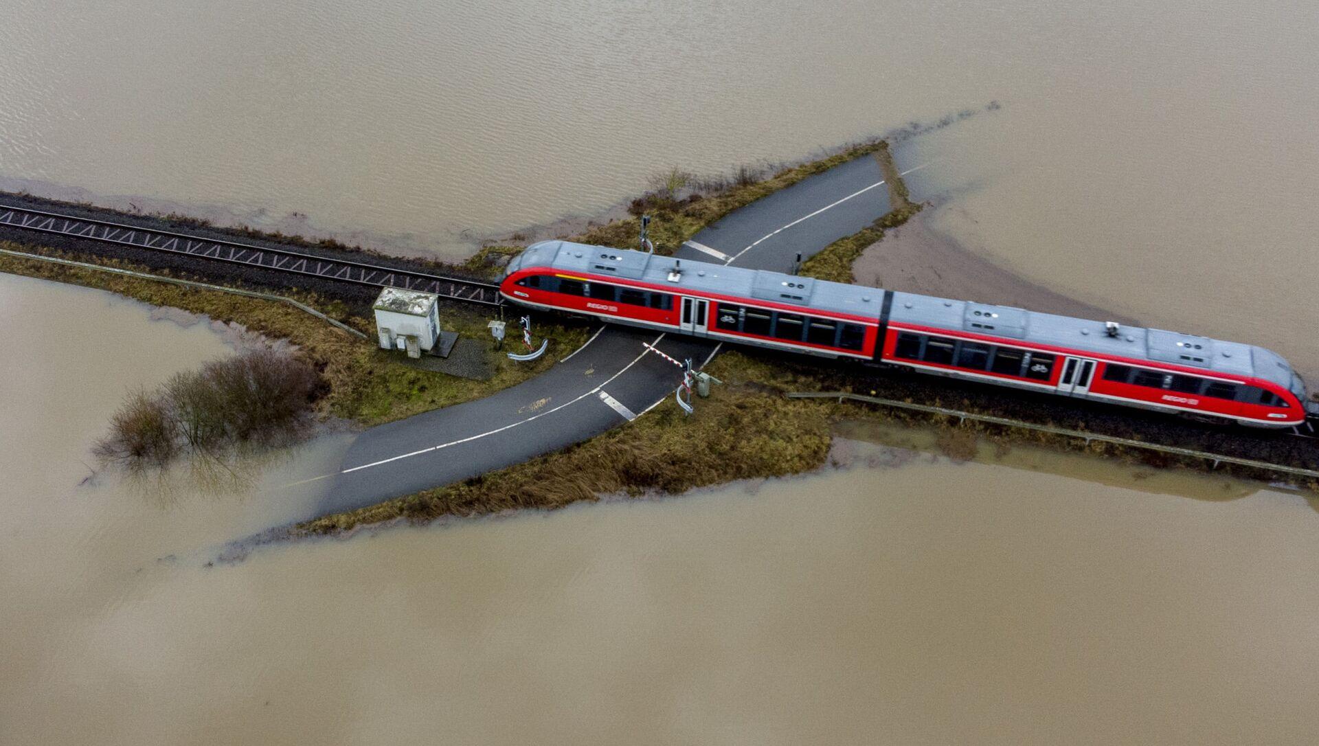 Поезд проезжает по железной дороге на затопленной местности в Германии  - Sputnik Italia, 1920, 13.05.2021