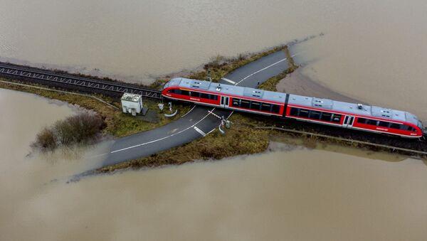Поезд проезжает по железной дороге на затопленной местности в Германии  - Sputnik Italia
