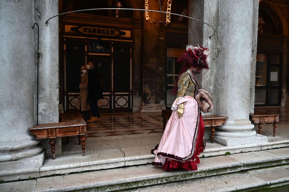 Una donna che indossa un costume da carnevale cammina vicino al caffè Florian chiuso in Piazza San Marco a Venezia il 6 febbraio 2021, nonostante il carnevale sia stato cancellato a causa della pandemia Covid-19