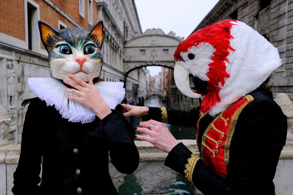 Le persone indossano maschere da carnevale vicino al Ponte dei Sospiri per celebrare il carnevale annuale di Venezia, che è stato cancellato quest'anno a causa della pandemia del coronavirus (COVID-19), a Venezia, Italia, il 7 febbraio 2021