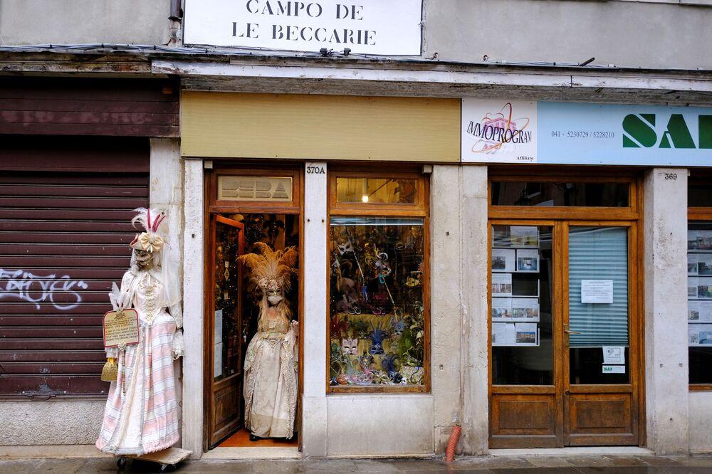 La proprietaria di una bottega artigiana di maschere che indossa un costume esce fuori per celebrare il carnevale di Venezia, che è stato cancellato quest'anno a causa della pandemia del coronavirus (COVID-19), a Venezia, Italia, il 7 febbraio 2021