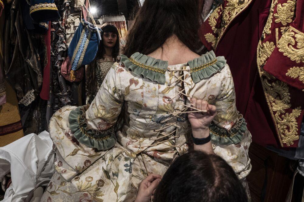 Una dipendente aiuta una festaiola a indossare un tradizionale costume da carnevale nel negozio 'La Bauta' a Venezia il 6 febbraio 2021