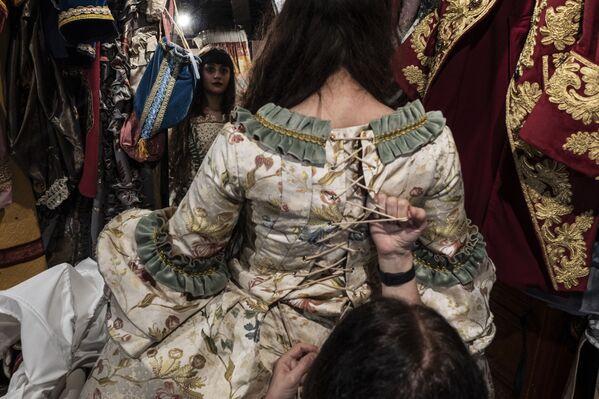 Una dipendente aiuta una festaiola a indossare un tradizionale costume da carnevale nel negozio 'La Bauta' a Venezia il 6 febbraio 2021 - Sputnik Italia