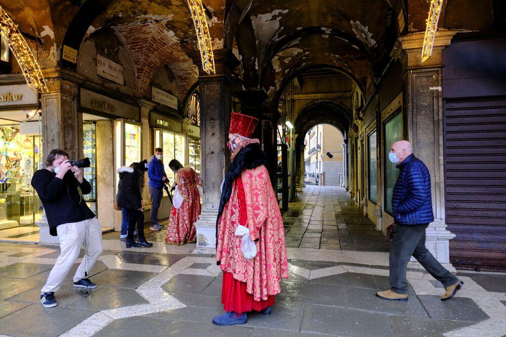 Un fotografo scatta una foto di una persona che indossa un costume da carnevale in Piazza San Marco a Venezia, Italia, il 7 febbraio 2021