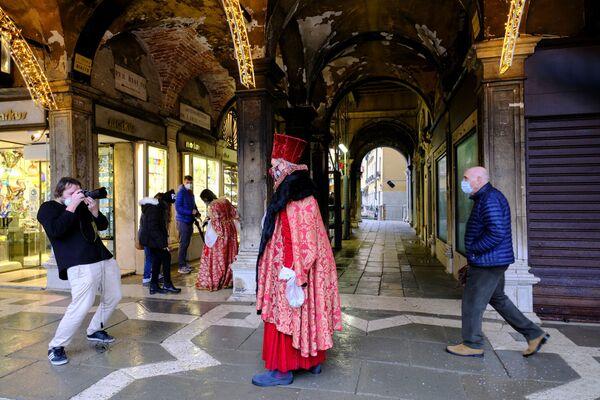 Un fotografo scatta una foto di una persona che indossa un costume da carnevale in Piazza San Marco a Venezia, Italia, il 7 febbraio 2021 - Sputnik Italia